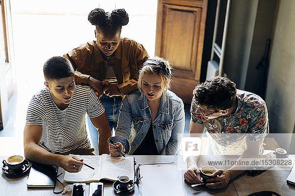 Schülerinnen und Schüler treffen sich im Café  lernen gemeinsam  mit Laptop und Smartphones