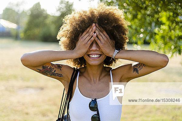 Lächelnde tätowierte junge Frau im Sommer  die mit ihren Händen Augen bedeckt