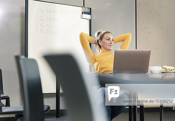 Casual businesswoman sitting at table in conference room leaning back