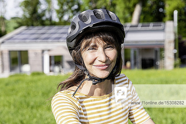 Portrait of smiling woman with bicycle helmet on a meadow in front of a house