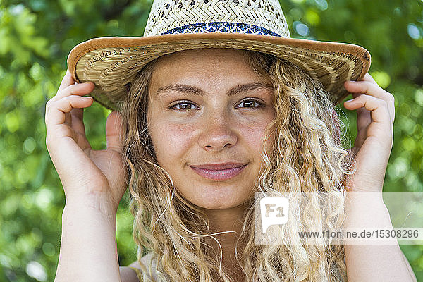 Portrait of smiling blond woman wearing straw hat  hands on hat