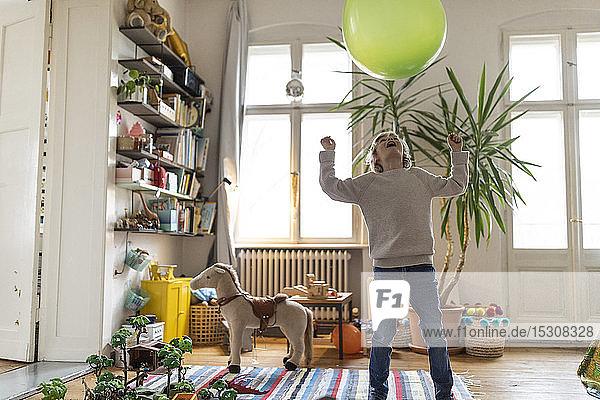 Junge spielt zu Hause mit einem Luftballon