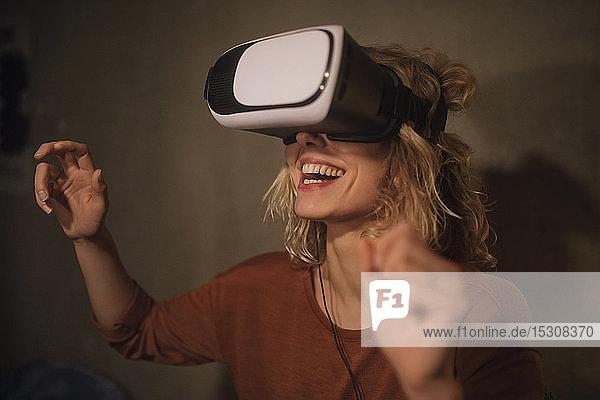Lachende junge Frau benutzt zu Hause eine Virtual-Reality-Brille