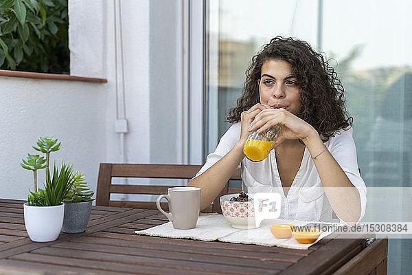 Junge Frau trinkt Orangensaft auf dem Balkon