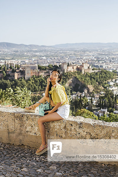 Young woman with camera sitting on a wall at the Alhambra  Granada  Spain