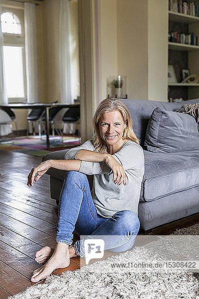 Porträt einer lächelnden reifen Frau  die barfuss auf dem Boden im Wohnzimmer sitzt