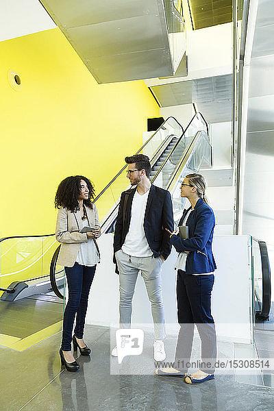 Junge Geschäftsleute im Gespräch an einer Rolltreppe