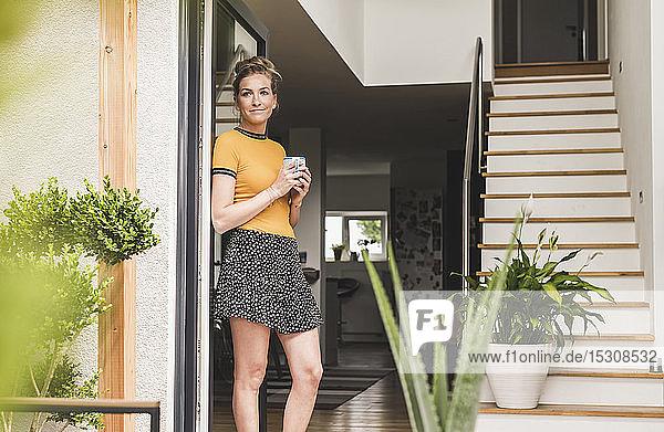 Frau hält Tasse Kaffee in der Hand und lehnt zu Hause an Terrassentür