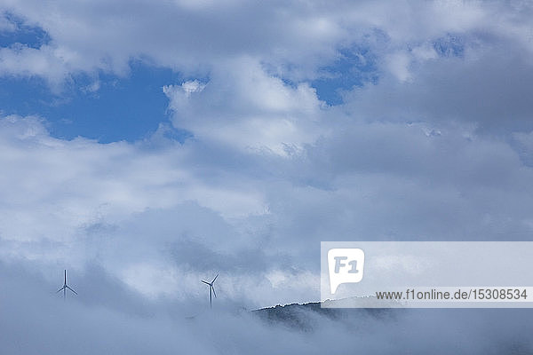Wind turbines on mountain amidst clouds against sky