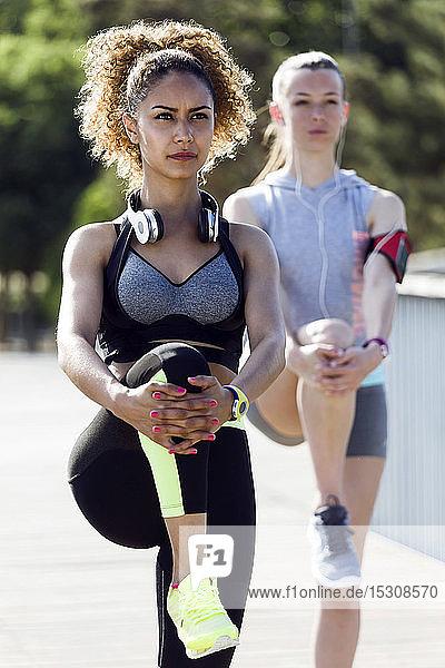 Zwei sportliche junge Frauen machen Dehnungsübungen