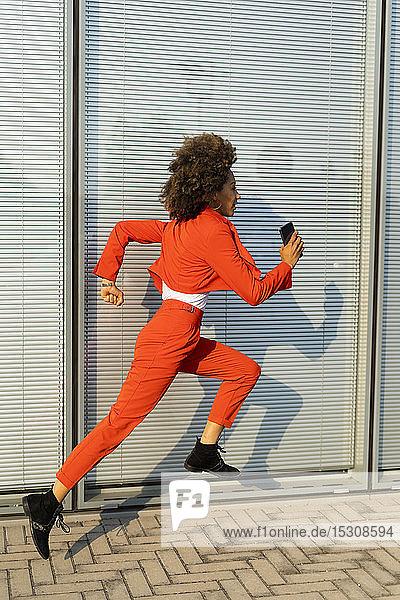 Laufende junge Frau mit Smartphone in modischem roten Hosenanzug