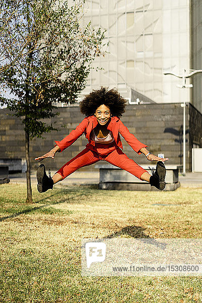 Porträt einer glücklichen jungen Frau in modischem roten Hosenanzug  die in die Luft springt