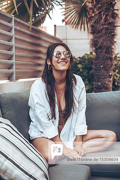 Junge Frau mit Hemd und Sonnenbrille sitzt auf einem Sofa vor dem Haus