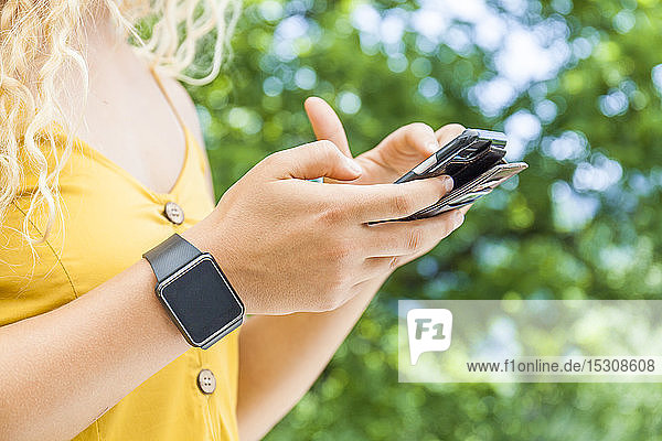 Woman using smartphone,  digital clock