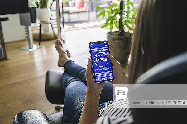 Junge Frau mit Smartphone mit Smart Home Control-Funktionen