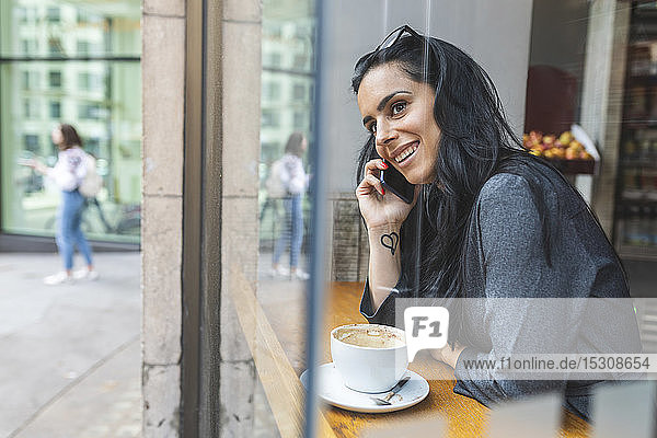 Smiling woman talking on the phone and sitting in a cafe