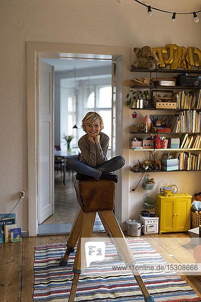 Porträt eines lächelnden Jungen  der in seinem Zimmer zu Hause auf einem Bock sitzt