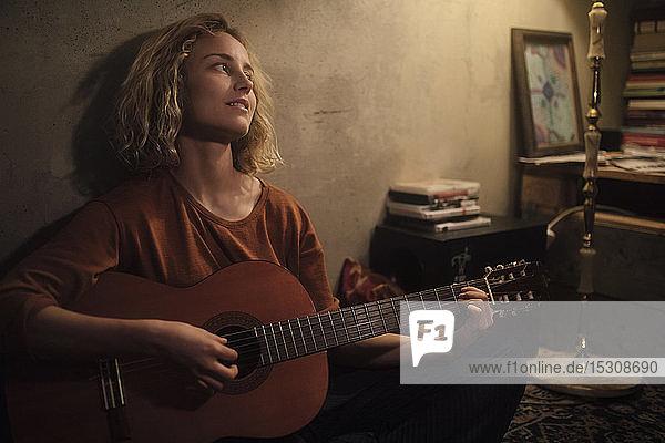 Junge Frau spielt zu Hause Gitarre