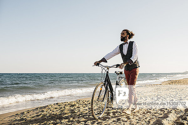 Well dressed man walking with his bike on a beach