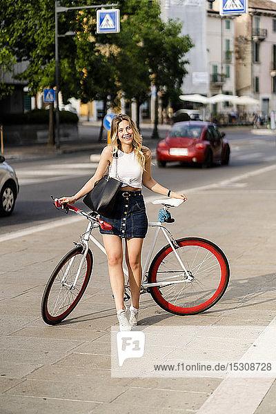 Porträt einer glücklichen jungen Frau mit Rennrad in der Stadt