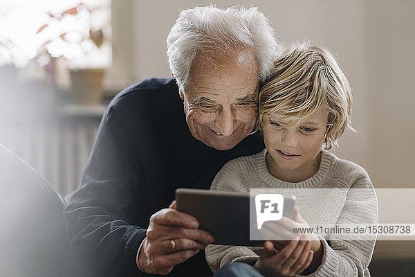 Großvater und Enkel verwenden zu Hause eine Tablette