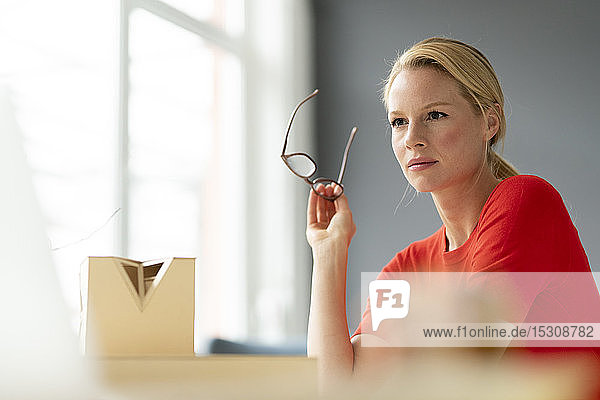 Thoughtful young woman in office with architectural model on desk