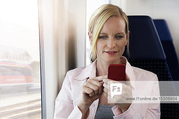 Frau benutzt Smartphone in einem Zug