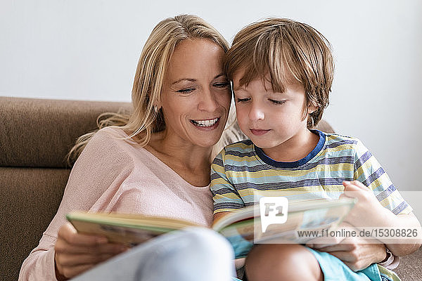 Mother and son reading a book together on couch at home