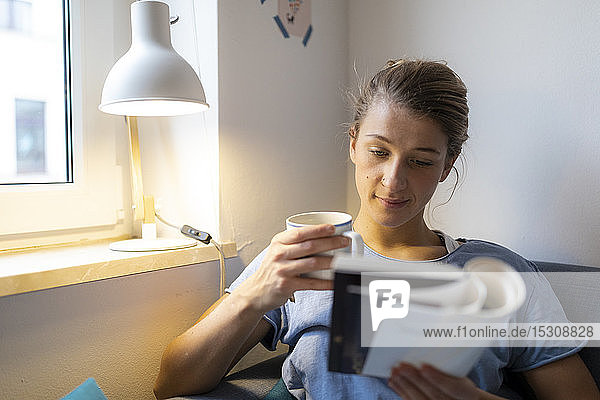 Young woman reading book on couch at home