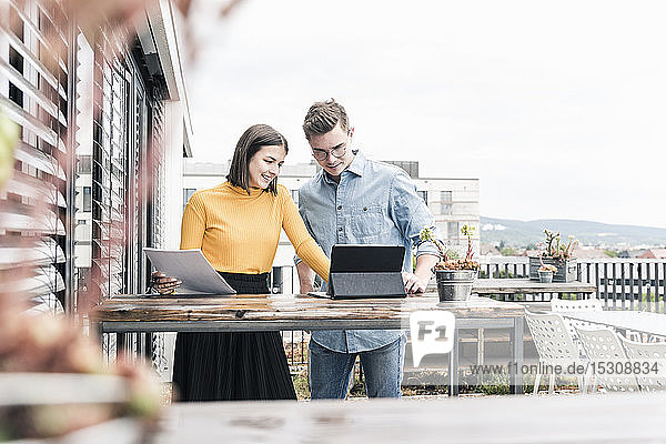 Casual businessman and woman with documents and tablet meeting on roof terrace