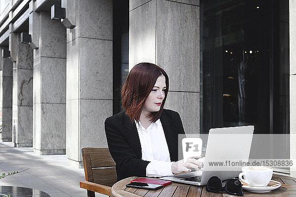 Geschäftsfrau  die im Café sitzt und einen Laptop benutzt