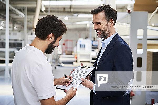 Mitarbeiter unterschreibt Dokument in einer Fabrik im Besitz eines Geschäftsmannes