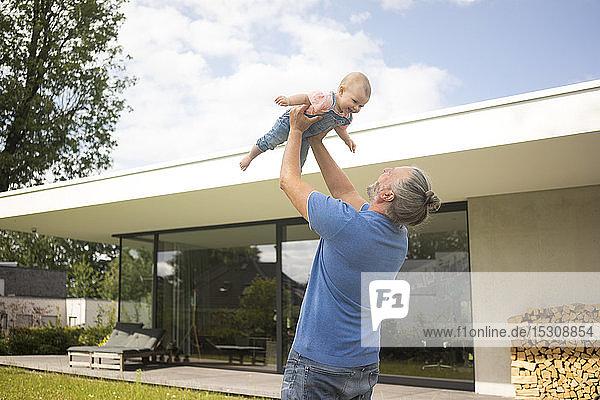 Glücklicher reifer Mann hebt kleines Mädchen im Garten seines Hauses hoch