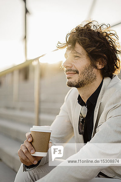 Smiling businessman with coffee to go sitting on stairs outdoors relaxing
