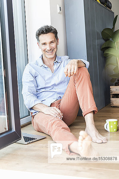 Mature man relaxing at home with a cup of coffee,  using laptop