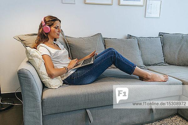 Entspannte junge Frau zu Hause auf der Couch mit Kopfhörern und Laptop