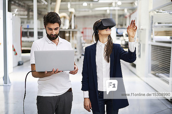 Man with laptop and businesswoman wearing VR glasses in factory