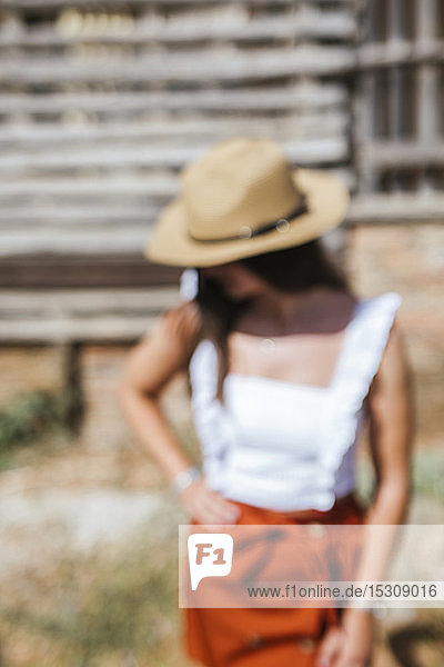 Portrait of blurred young girl wearing straw hat