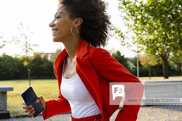 Lächelnde junge Frau mit Smartphone in modischem roten Hosenanzug