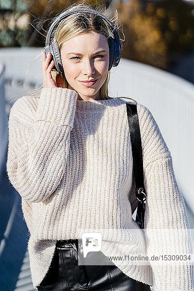 Porträt einer jungen Frau  die im Freien mit Kopfhörern Musik hört