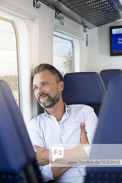 Ein reifer Mann sitzt in einem Zug und schaut aus dem Fenster