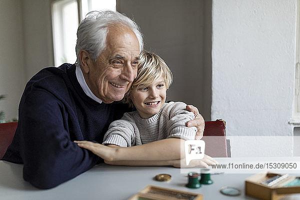 Uhrmacher und sein Enkel am Tisch sitzend