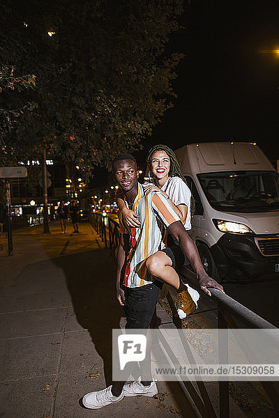 Happy young couple on the street at night in the city