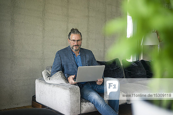 Portrait of mature businessman sitting on couch at home using laptop