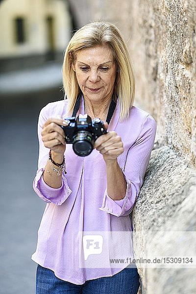 Ältere Frau mit einer Spiegelreflexkamera in der Stadt