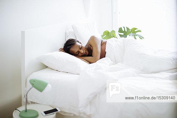 Zu Hause im Bett schlafende Frau