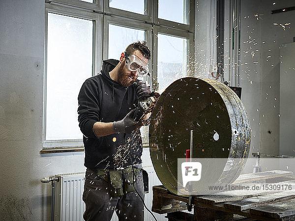 Am Metallbehälter arbeitender Mann mit Schleifmaschine