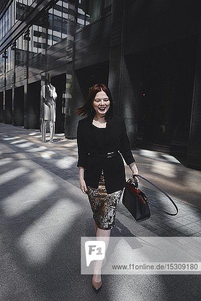 Stilvolle Frau geht in der Stadt spazieren
