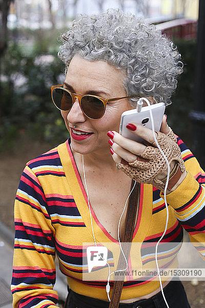 Porträt einer modischen  reifen Frau  die ihr Smartphone im Freien benutzt