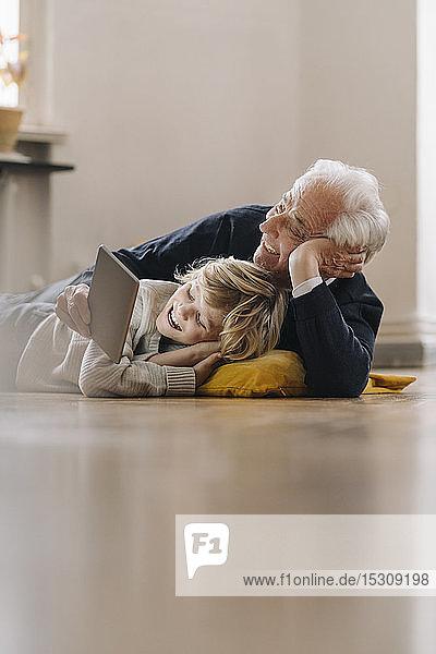 Glücklicher Großvater und Enkel  die zu Hause mit einer Tablette auf dem Boden liegen